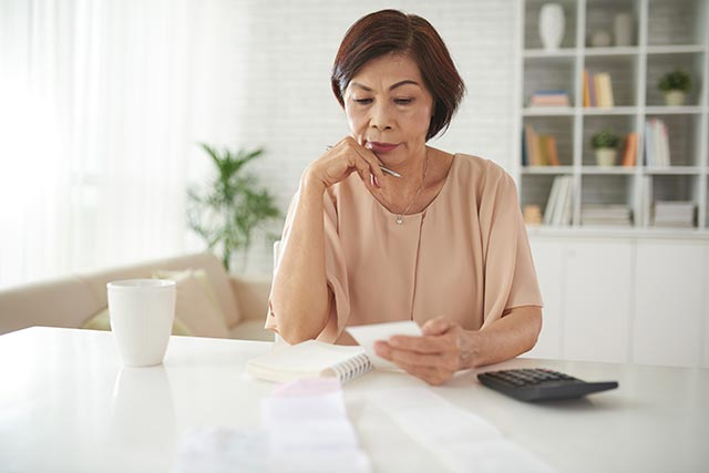 A woman calculating her finances and worrying about the burden of illness
